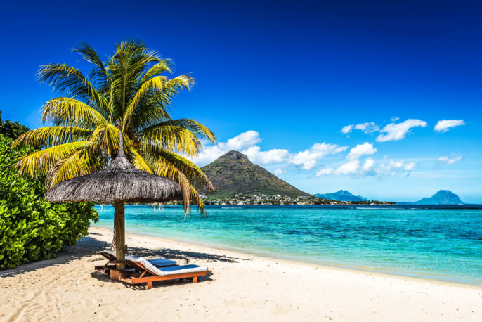 Loungers and umbrella on tropical beach in Mauritius
