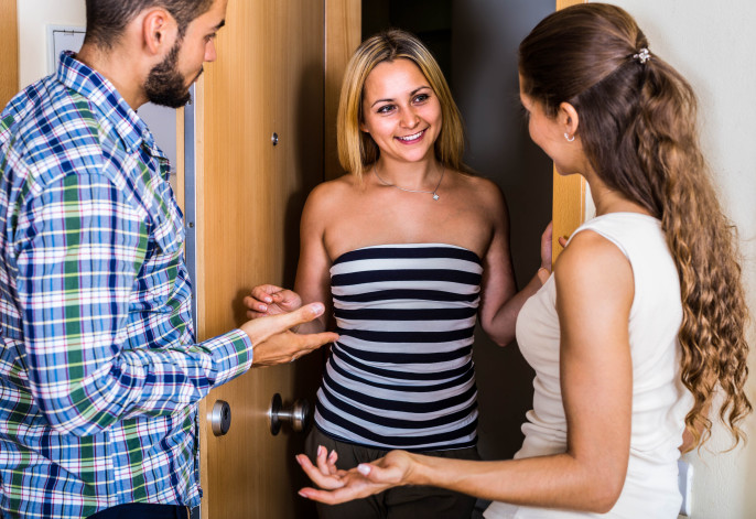 Happy young couple welcoming smiling friend at the doorway shutterstock_327993164-2