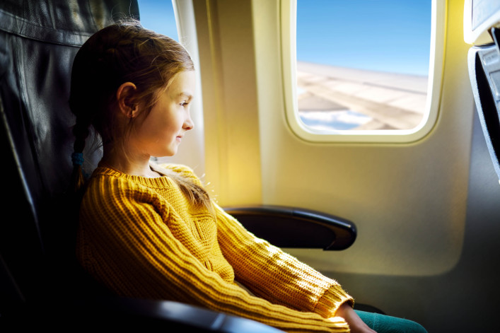 Adorable little girl traveling by an airplane shutterstock_402427960-2