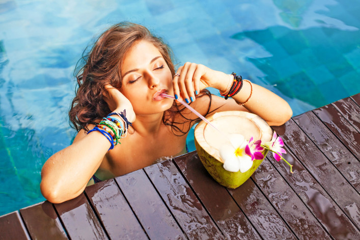 Woman drinking a coconut cocktail with closed eyes