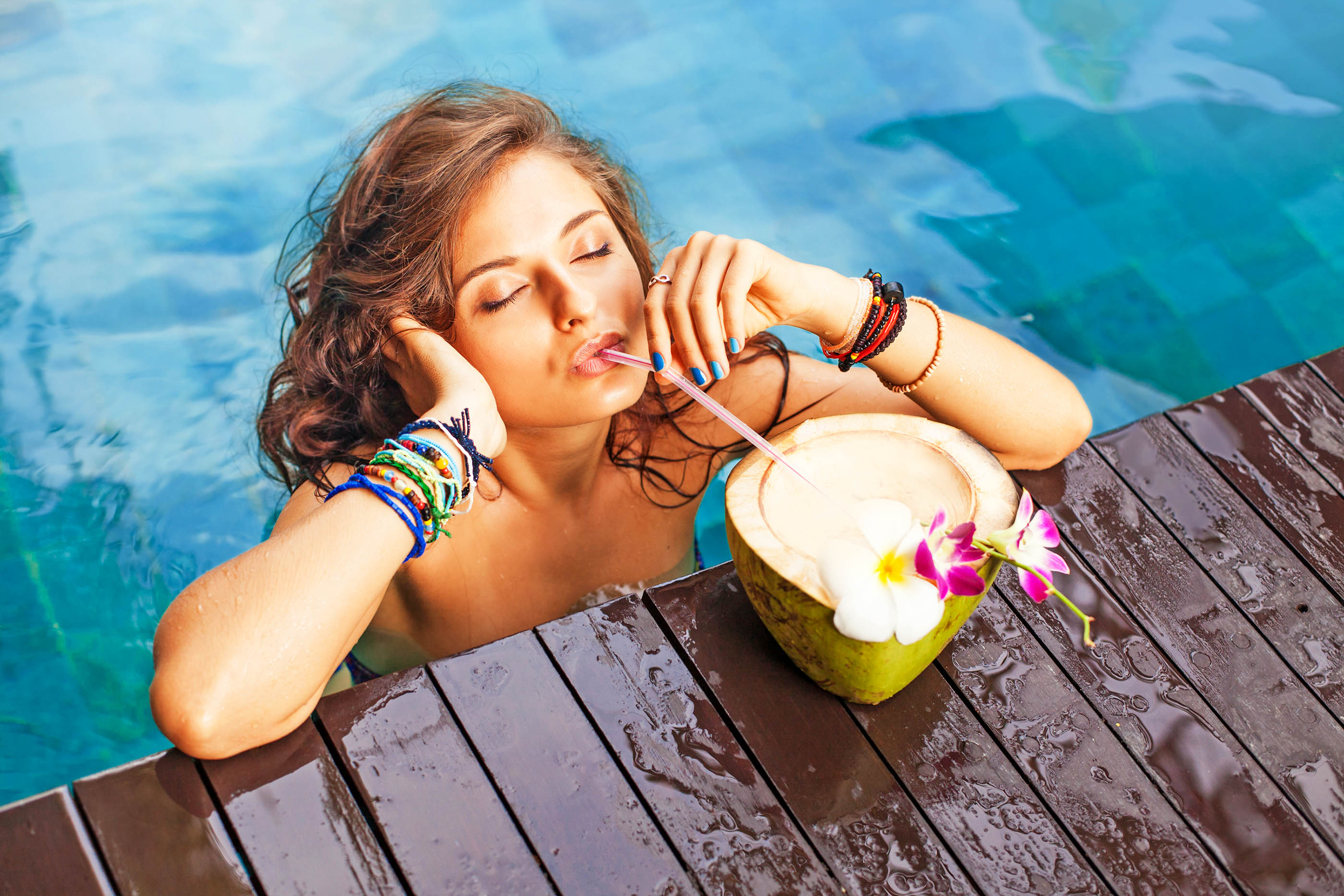Beautiful girl standing on an edge of swimming pool and drinking coconut cocktail