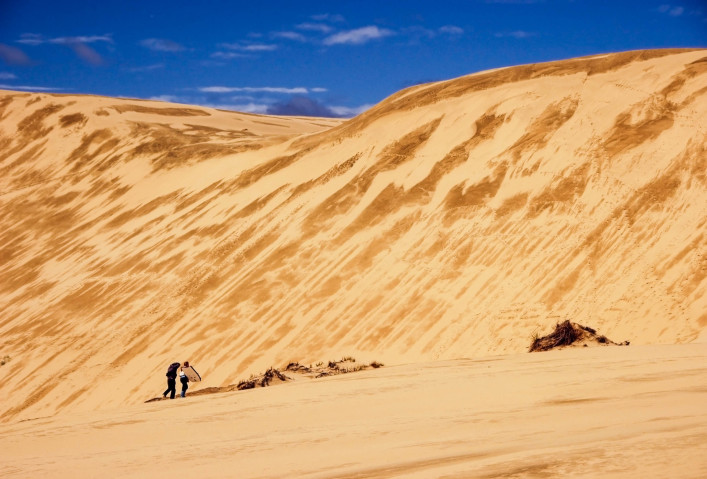 Two sandboarders walking up the sand dune