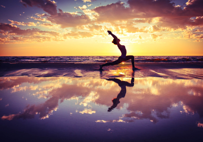 silhouette of woman practicing yoga on the beach at sunset shutterstock_304371815-2