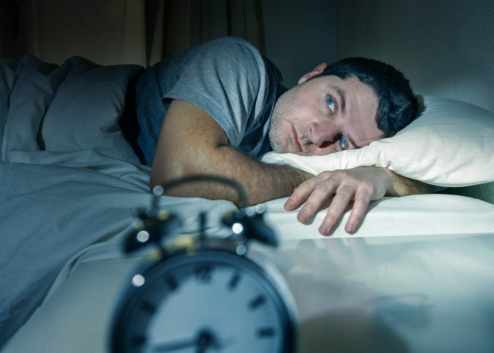 young man in bed with eyes opened shutterstock_171835172-2