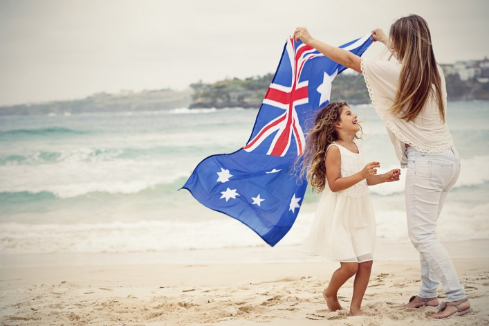Mother and daughter with Australian flag at the beach