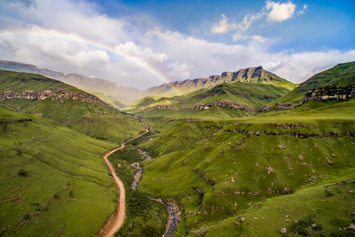 Fairy tale stunning rainbow over very wide valley called Sani Pass at South Africa and Lesotho border shutterstock_381160156