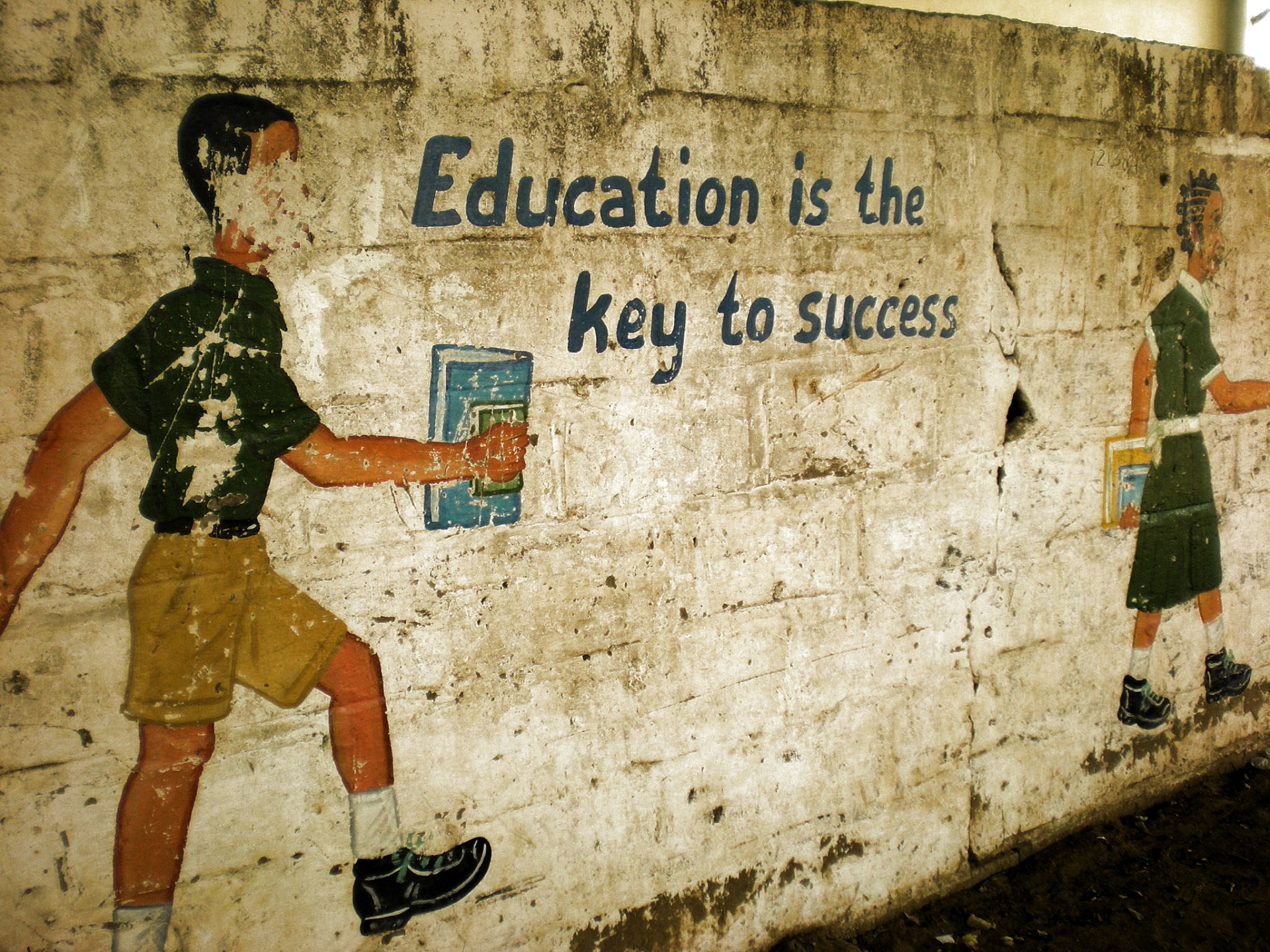 "An einer Wand steht geschrieben: ""Education is the key of success""."
