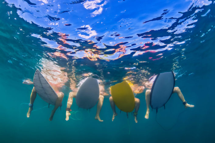 Underwater photo of surfers sitting on surf boards