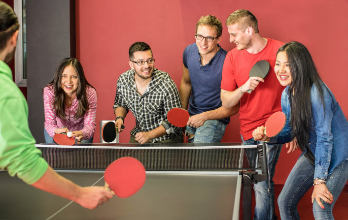 Group of happy young friends playing ping pong table tennis shutterstock_270733406-2
