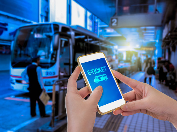 E-Ticket - Hand holding mobile phone with E-Ticket word with blur bus terminal background shutterstock_360686624-2