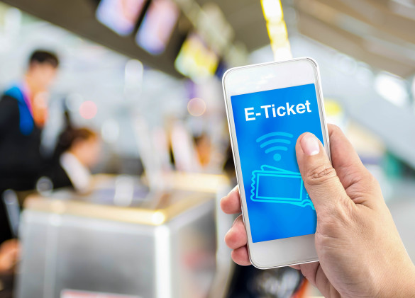 E-Ticket - Hand holding mobile with E-Ticket with blur airport check-in background shutterstock_300059927-2