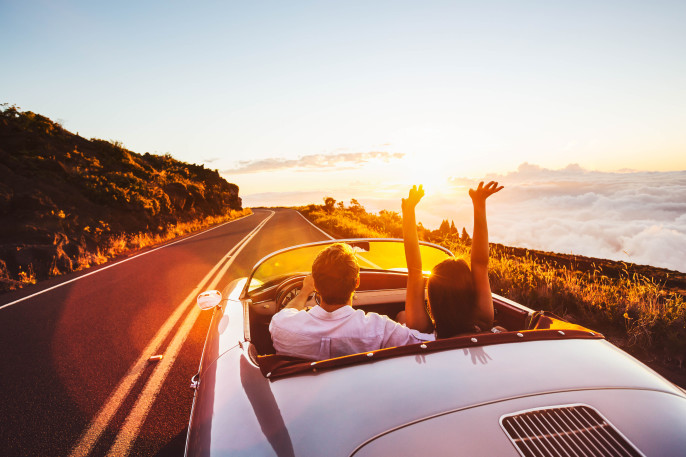 Happy Couple Driving on Country Road into the Sunset in Classic Vintage Sports Car shutterstock_305567459-2