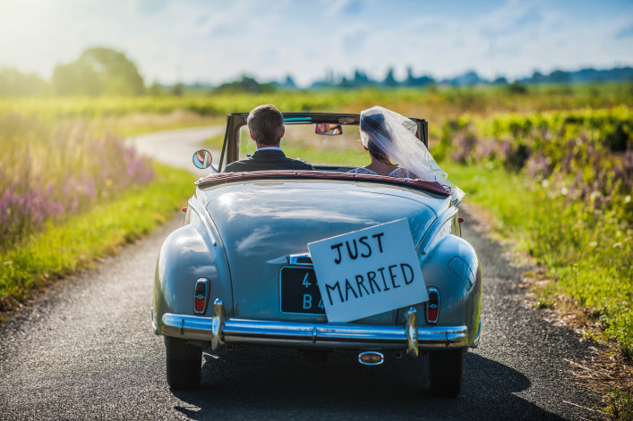 Couple is driving a convertible retro car on a country road for their honeymoon shutterstock_261887489-2
