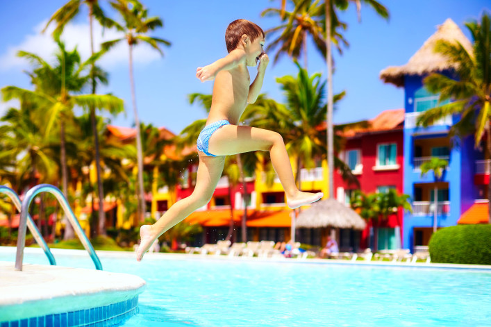 happy excited kid jumping in pool on summer vacation shutterstock_329004038-2