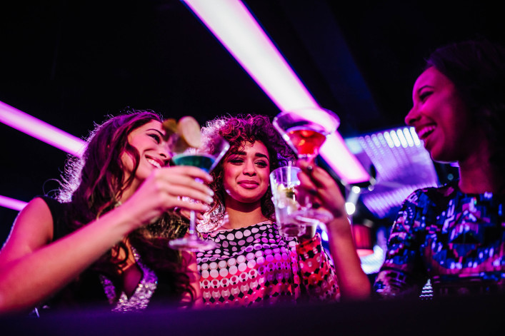 Young friends enjoying night club party toasting with drinks