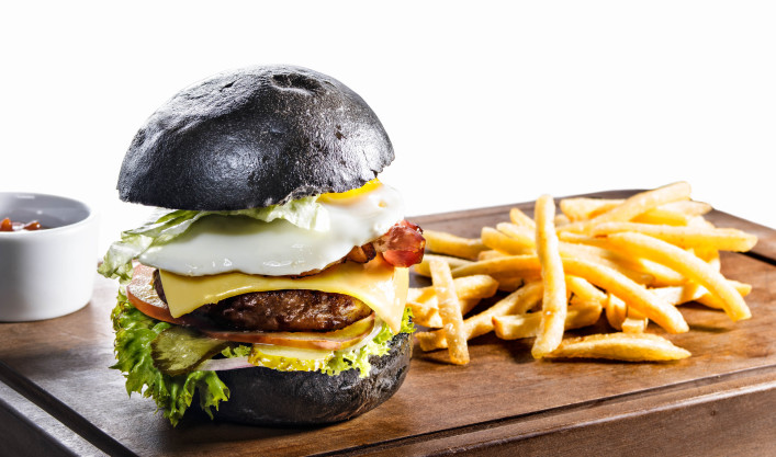 Black burger and french fries isolated on white