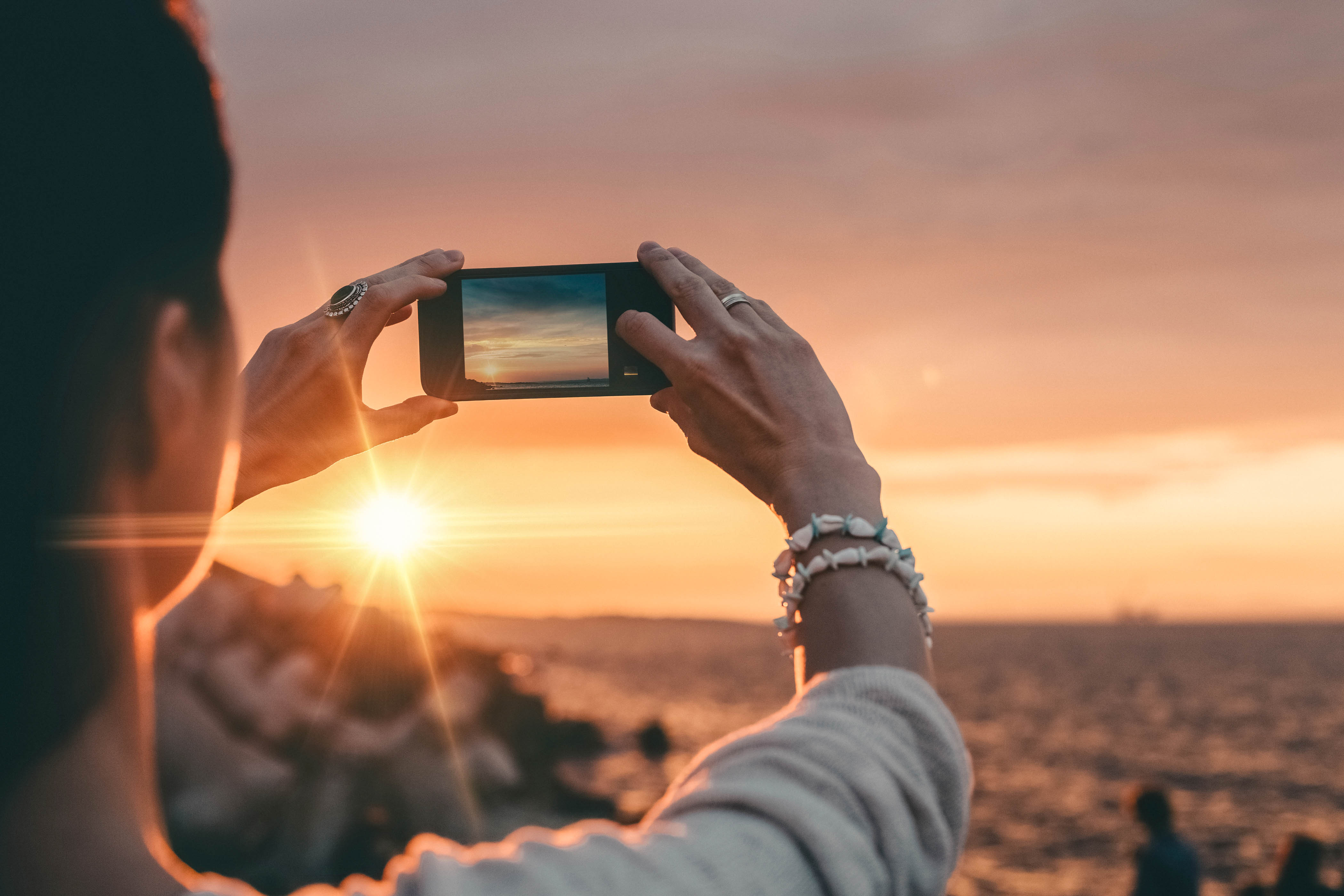 Girl taking a photo of the sunset with mobile phone