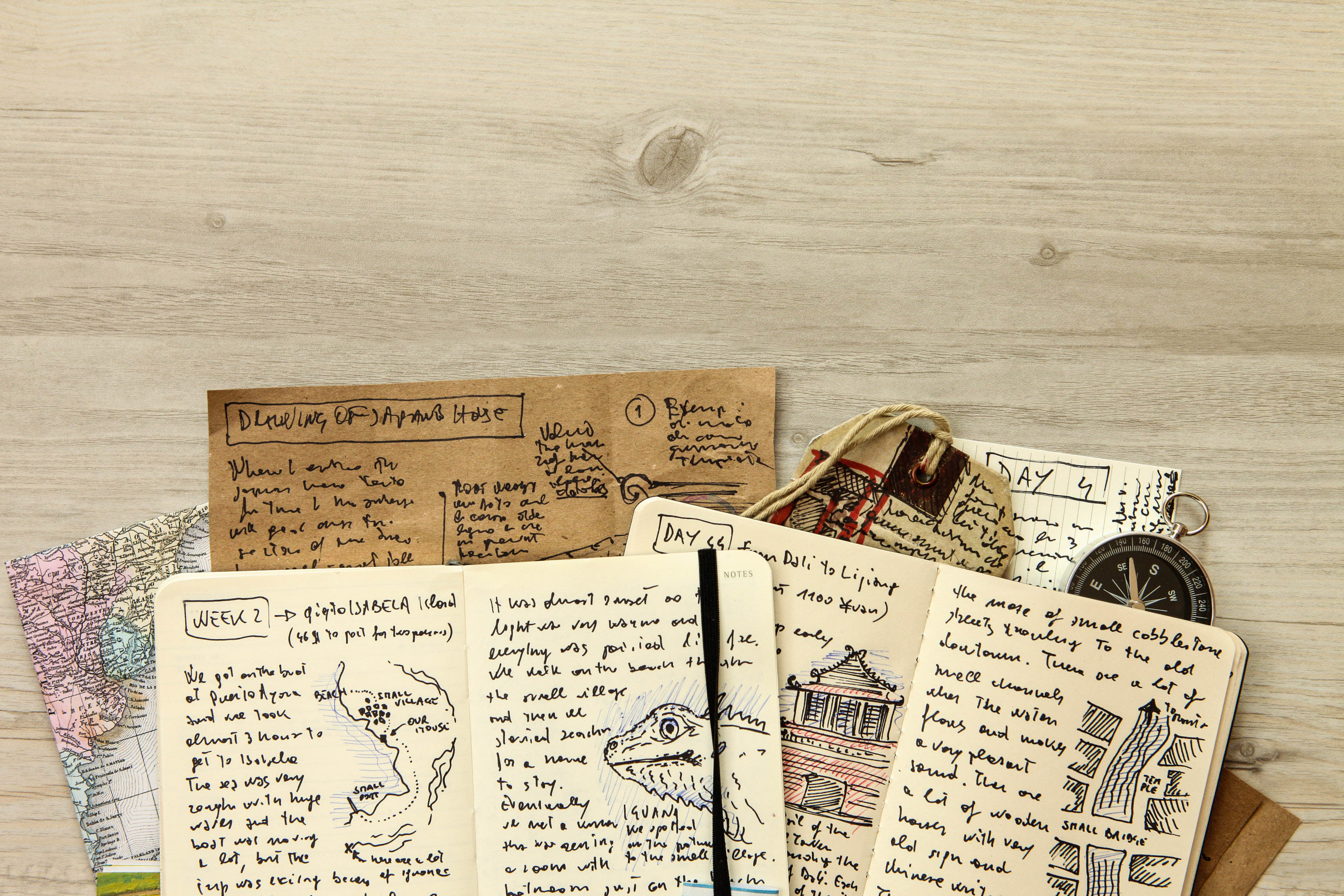 Handwritten travel diary and journal with drawings, reports and memories, stories about adventurous journeys with maps, directions and notes. Compass, tickets, tags and other travel items. On a wooden background with copy space on top side.