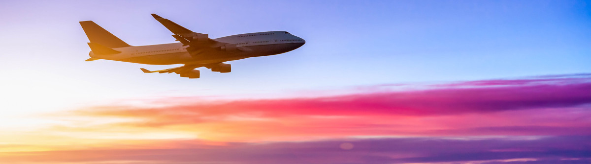 Airplane in the sky at sunrise shutterstock_209155915-2