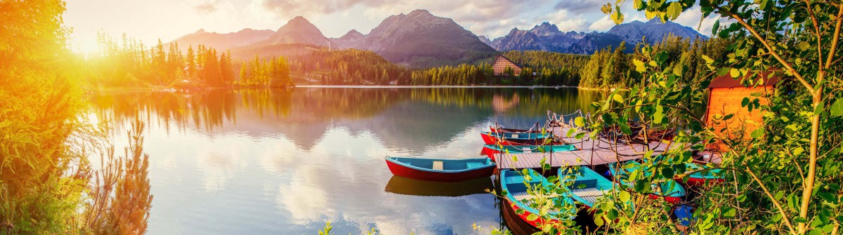Boat on the dock surrounded mountains. Fantastic Shtrbske Pleso