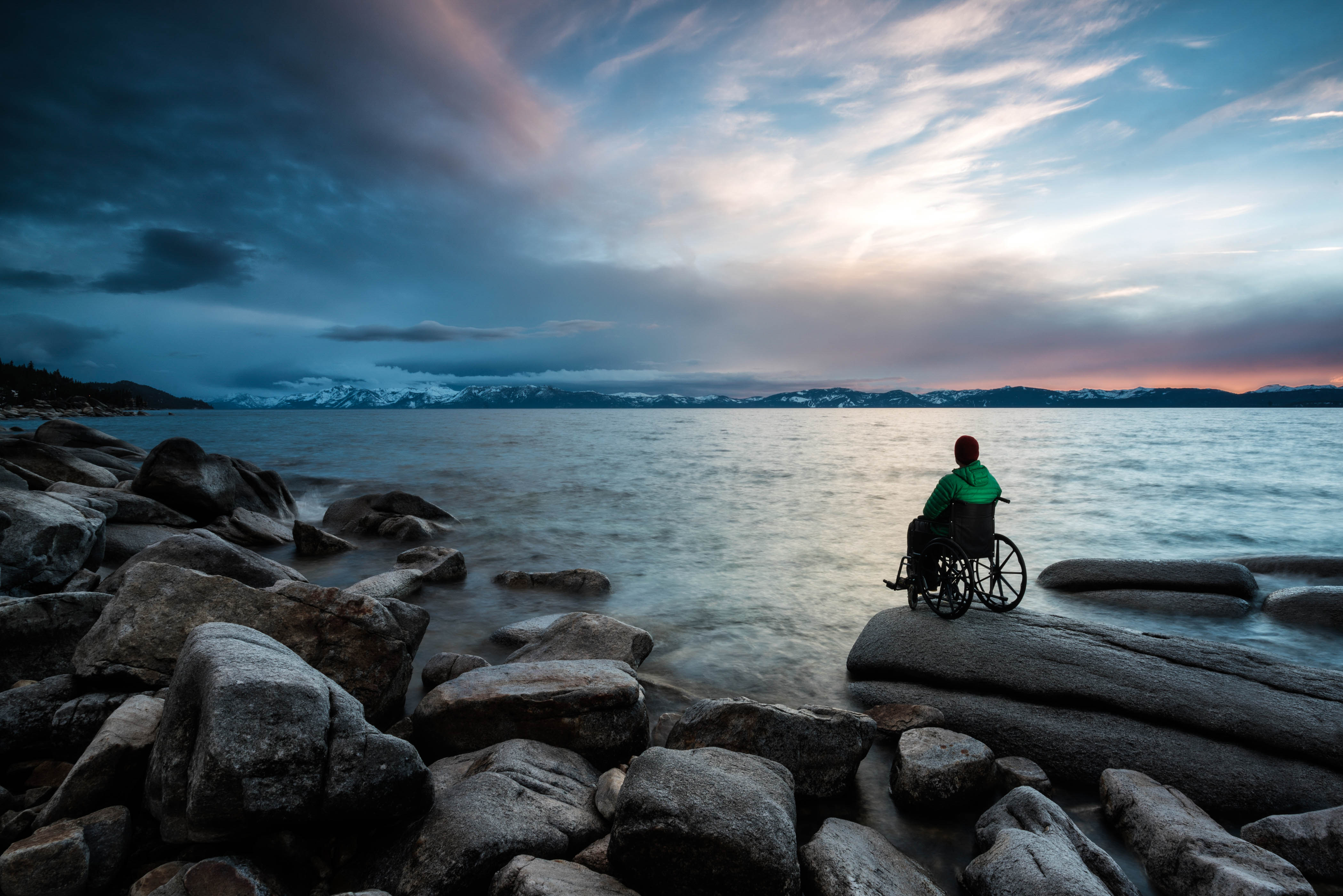 A disabled athlete looking off into the distance during sunset. Location Lake Tahoe CA USA
