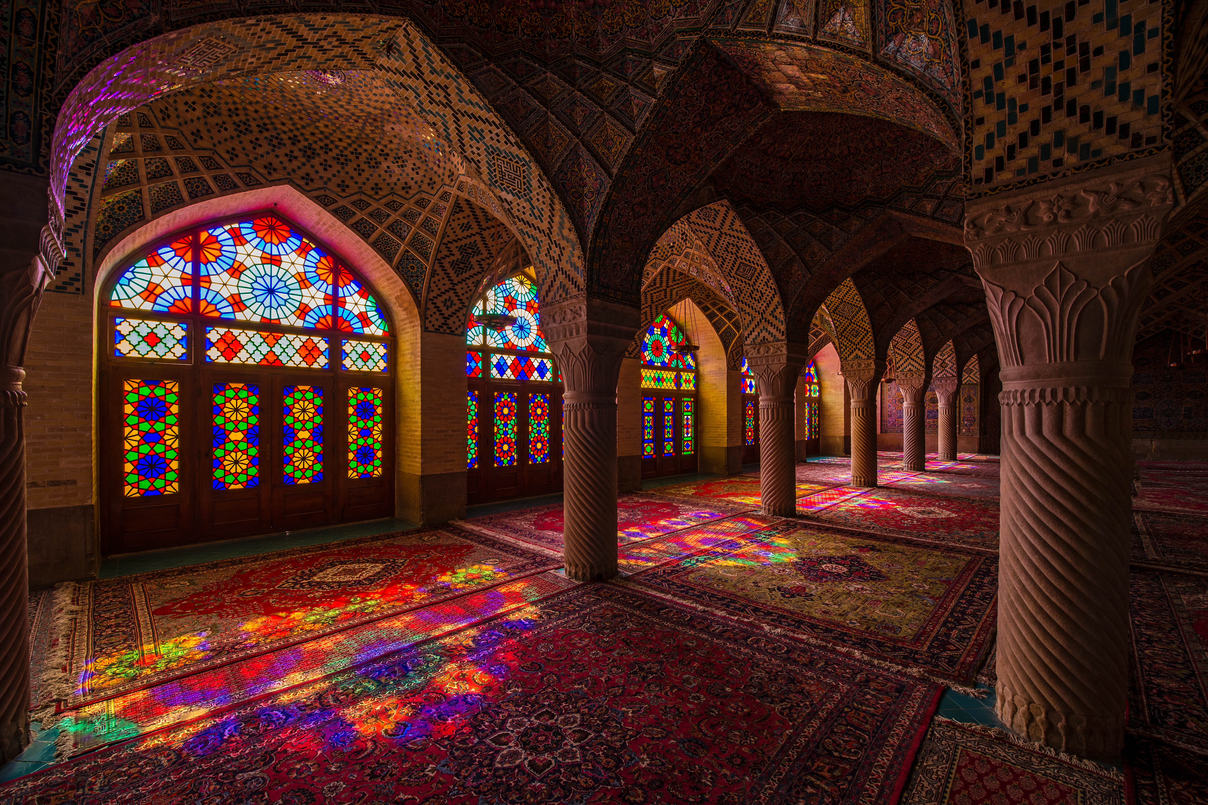 "Interior with beautiful and artistic windows with stained glass inside the Nasir ol Molk Mosque (also ""Pink Mosque) in Shiraz, Iran. The Nasir ol Molk Mosque is one of the main sights of Shiraz. The mosque was built during the Qajar era between 1876 and 1888.The nickname ""Pink Mosque"" is going back to the considerable pink color tiles for its interior design."