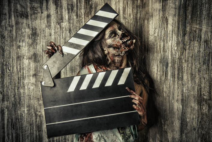Filming a horror movie. Female zombie holding clapper board shutterstock_242381503-2