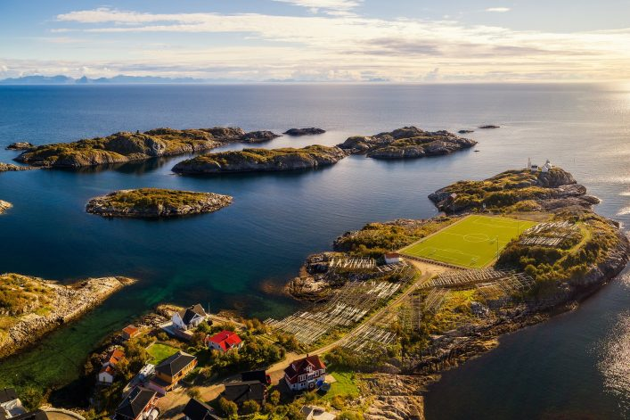 Aerial view of Henningsvaer, its scenic football field and many fish racks at sunset_ Lofoten archipelago in Norway shutterstock_726172498