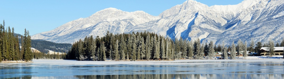 Sunny view of the reflection of mountains in freezing Lac Beauvert in Jasper National Park, Alberta, Canada shutterstock_234029716