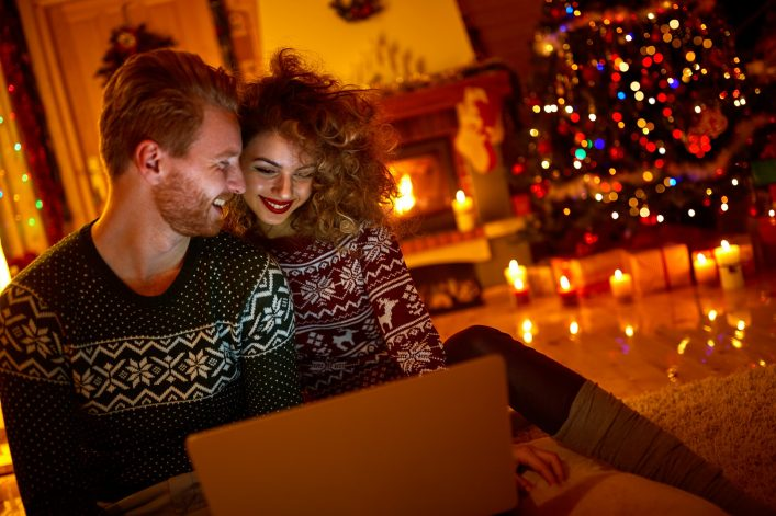 Young couple looking on laptop on Christmas eve shutterstock_502791301