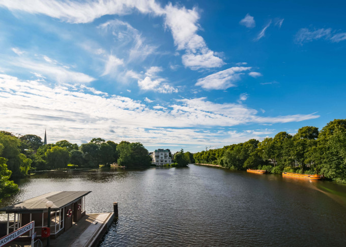 Alster Lake in Hamburg Germany on a summer day. Beautiful view at old building in city park near famous Krugkoppel bridge and ferry station, image for travel business_shutterstock_518639782