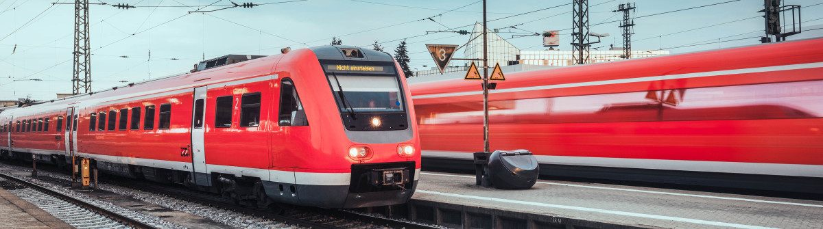 Railway station with modern red passenger train. Industrial landscape