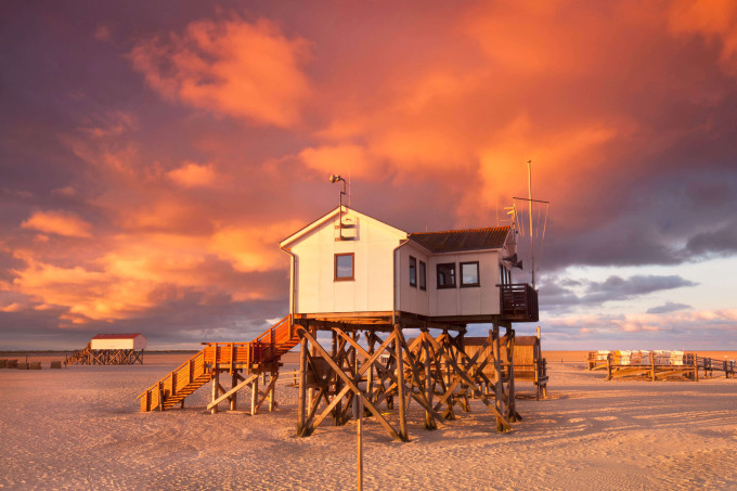 Typical pile house at the beach of St. Peter Ording north sea coast, Germany, sunrise_shutterstock_292636145_klein