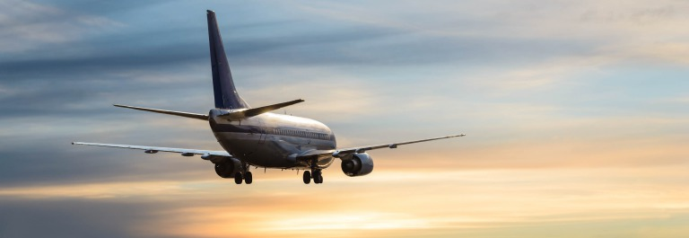 Airplane with landing gear in cloudy sky at sunset shutterstock_538431271-2