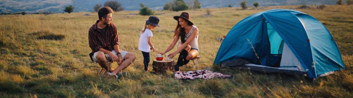 Young people camping with a baby girl
