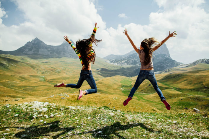 two girls happy jump in mountains