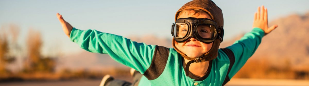 young-boy-with-goggles-imagines-flying-on-suitcase_iStock_597927618