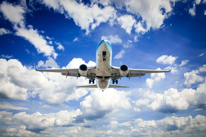 Airplane flying in the blue sky with clouds iStock_27146639_LARGE-2