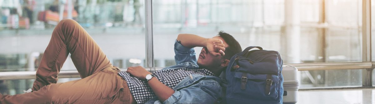 Asian-young-man-waiting-at-the-airport-terminal-for-his-delay-flight-shutterstock_1006883185