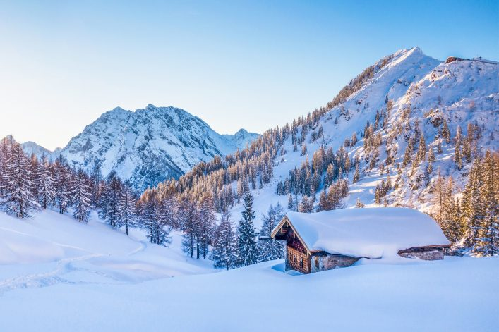 Winter wonderland in the Alps with mountain chalet at sunset
