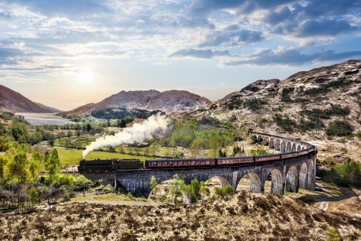 Glenfinnan Railway Viaduct in Scotland with the Jacobite steam train against sunset over lake shutterstock_422357125
