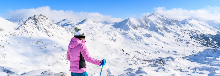 Young-woman-skier-standing-on-ski-slope-and-looking-at-snowy-mountains-in-Obertauern-Austria-shutterstock_566198236