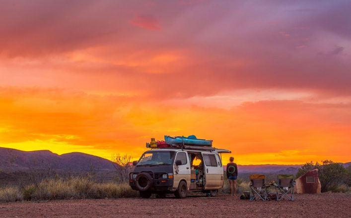 Mädchen steht neben ihrem Campervan und schaut den Sonnenuntergang an in den West Macdonnell Ranges im Northern Territory in Australien.