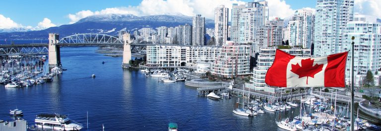 Canadian-flag-in-front-of-view-of-False-Creek-and-the-Burrard-street-bridge-in-Vancouver-Canada._549375997