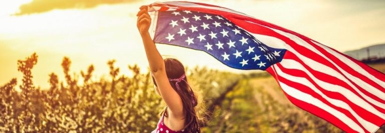 Girl-Through-a-Car-Sunroof-Waving-with-USA-Flag-iStock_93831847_XLARGE-2