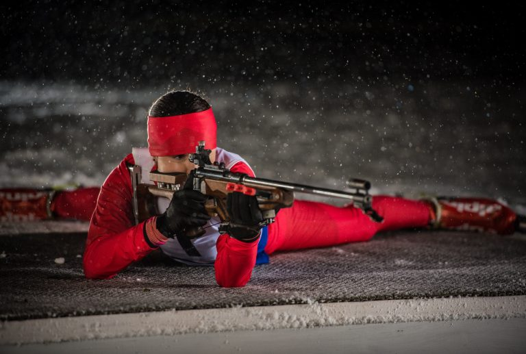 Athletic woman with biathlon rifle