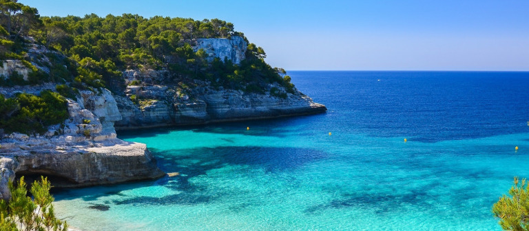 Secluded-beach-with-turquoise-sea-water-Cala-Mitjaneta-Menorca-island-Spain-shutterstock_189270002