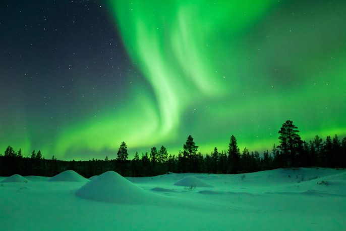 Aurora borealis over snowy landscape winter, Finnish Lapland