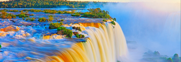 Impressive Iguacu falls landscape, blurred motion from long exposure at dramatic sunset – Idyllic Devil's Throat – international border of Brazilian Foz do Iguacu, Parana, Argentina Puerto Iguazu, Misiones and Paraguay – South America