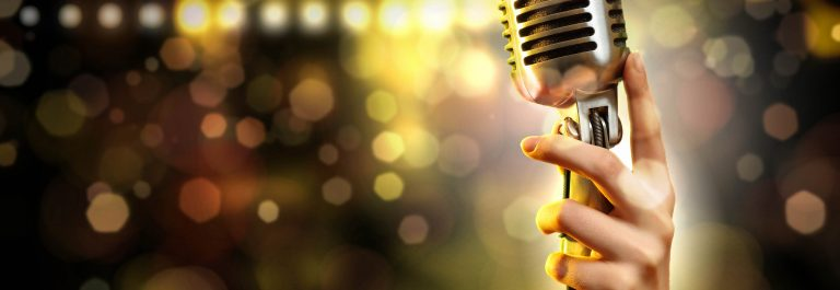 Female-hand-holding-a-single-retro-microphone-against-colourful-background-shutterstock_136602104-2